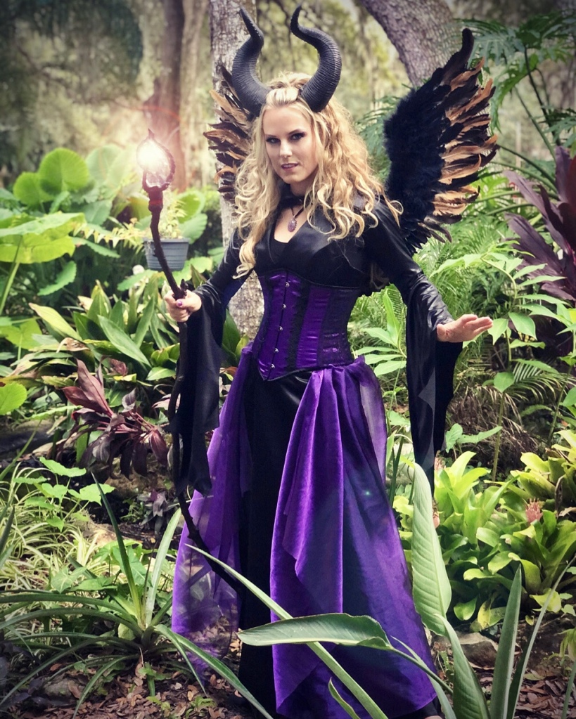 Maleficent cosplay with glowing wizard staff